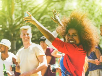 Multiracial young people dancing in forest party in summer time - Cheerful multi ethnic friends drinking outdoor - New music entertainment trends  - Soft focus on black girl - Vintage retro editing