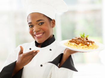 beautiful afro american chef presenting spaghetti