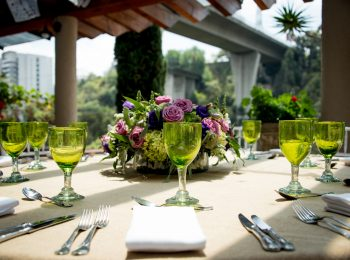 Stylish table setting for an open-air wedding with green wineglasses, silverware and linen on a table on a sunny urban patio